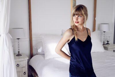 Młoda piękna kobieta w granatowej koszuli nocnej w sypialni